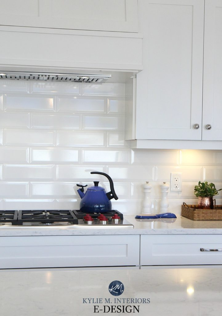 White kitchen cabinets with white bevelled subway tile backsplash, navy blue le creuset accents. Kylie M Interiors Edesign, online paint color consulting and blogger