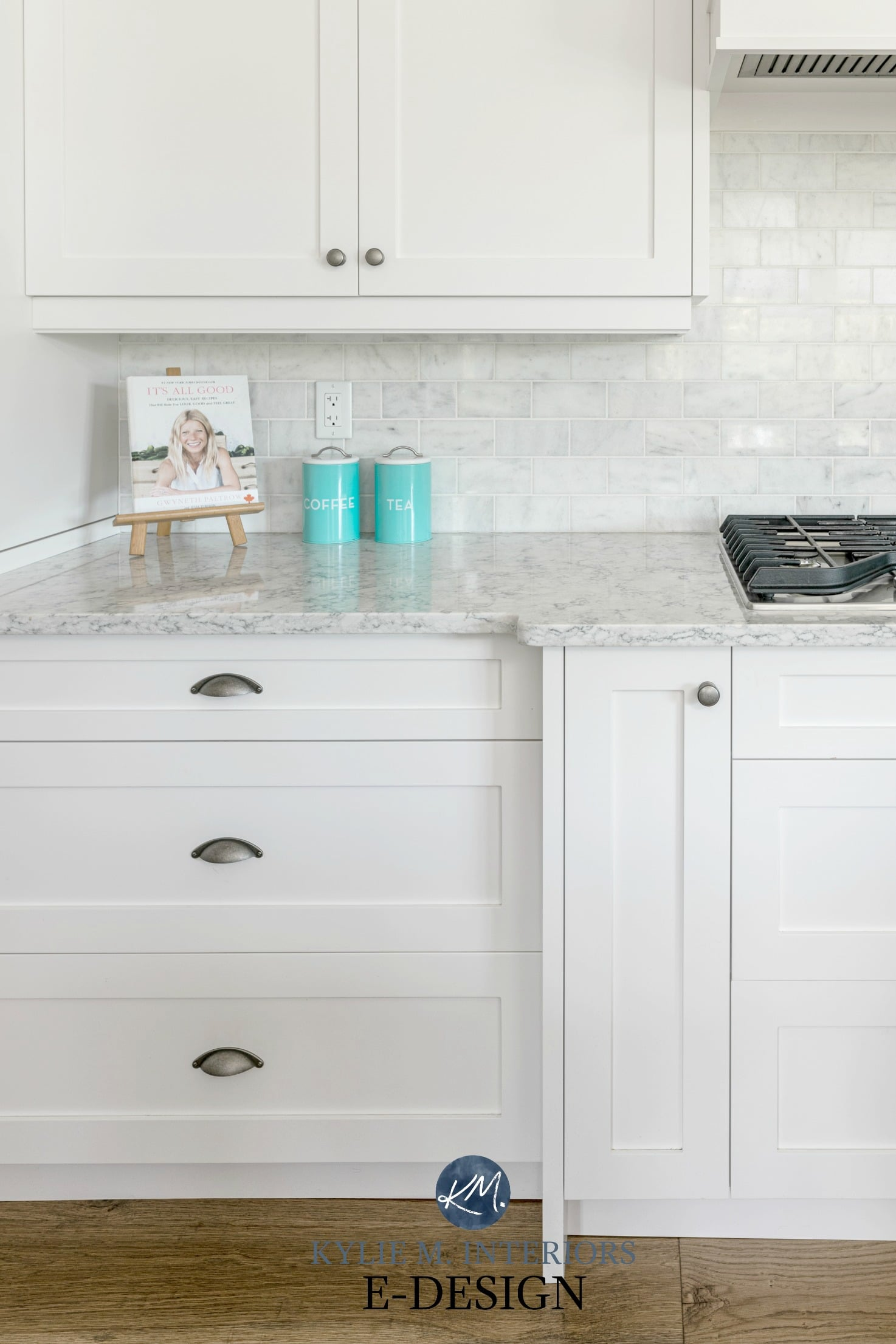 Kitchen cabinets painted Sherwin High Reflective White, marble backsplash, white quartz, home decor on countertop. Pewter hardware. Kylie M Interiors Edesign, online paint colour consulting