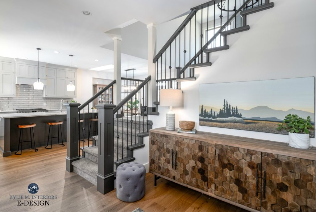Open layout entryway, kitchen stairwell. warm gray kitchen cabinets, white oak flooring and painted stair railing with carpet. Kylie M Interiors Edesign, online paint colour consulting