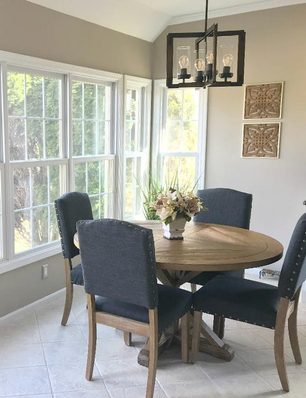 Eating nook in kitchen with round table, upholstered chairs. Best beige paint colour on walls, Sherwin Williams Balanced Beige. Kylie M Interiors Edesign, online paint colour expert