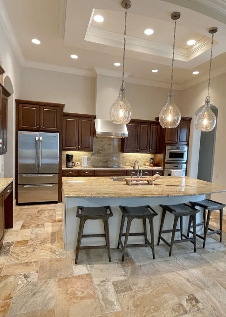 Kitchen with dark wood cabinets, travertine floor, Sherwin Williams Canvas Tan paint colour, island and pendants. Kylie M Interiors Edesign