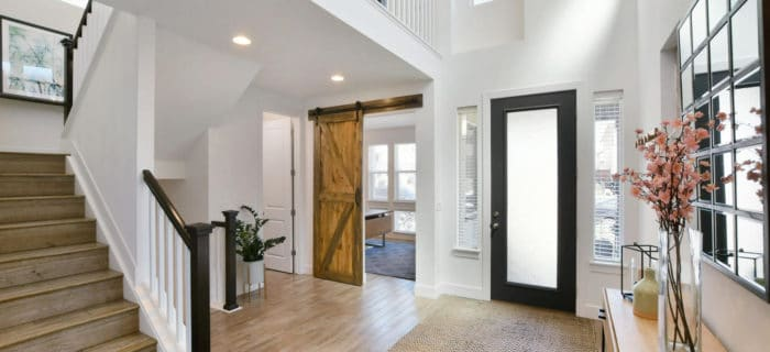 2 storey entryway or foyer, white walls, Sherwin Williams Pure White, black front door, wood stairs, sliding barn door. Kylie M Interiors Edesign, online paint colour, virtual diy decorating ideas