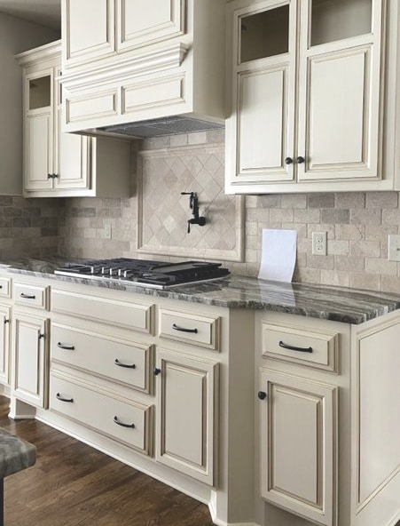 Antique White cream cabinets with dark countertop and travertine TOO WARM