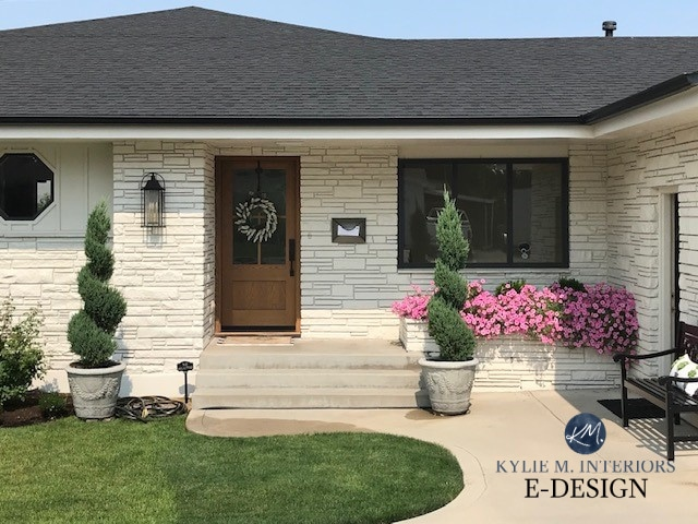 Exterior 1960 stone painted cream off white paint colour, wood look garage door, dark gray black roof. Kylie M Interiors Edesign, online paint color consulting and diy decorating advice (2)