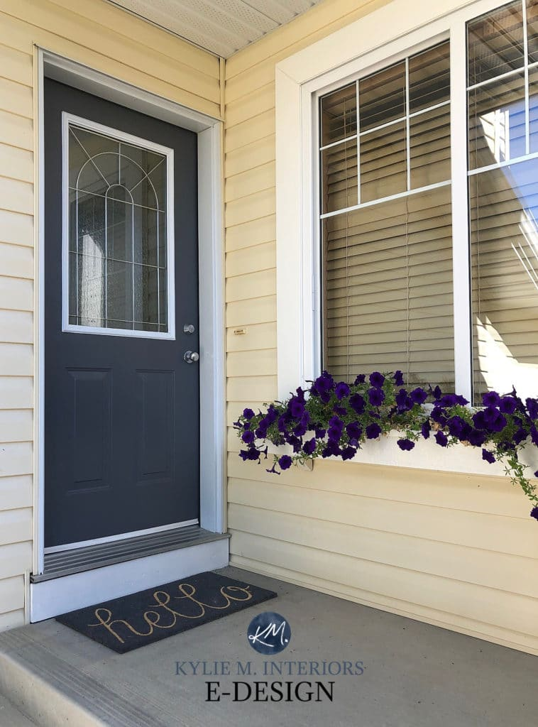 Front door painted Sherwin Williams Cyberspace, navy blue with yellow siding. Kylie M INteriors Edesign