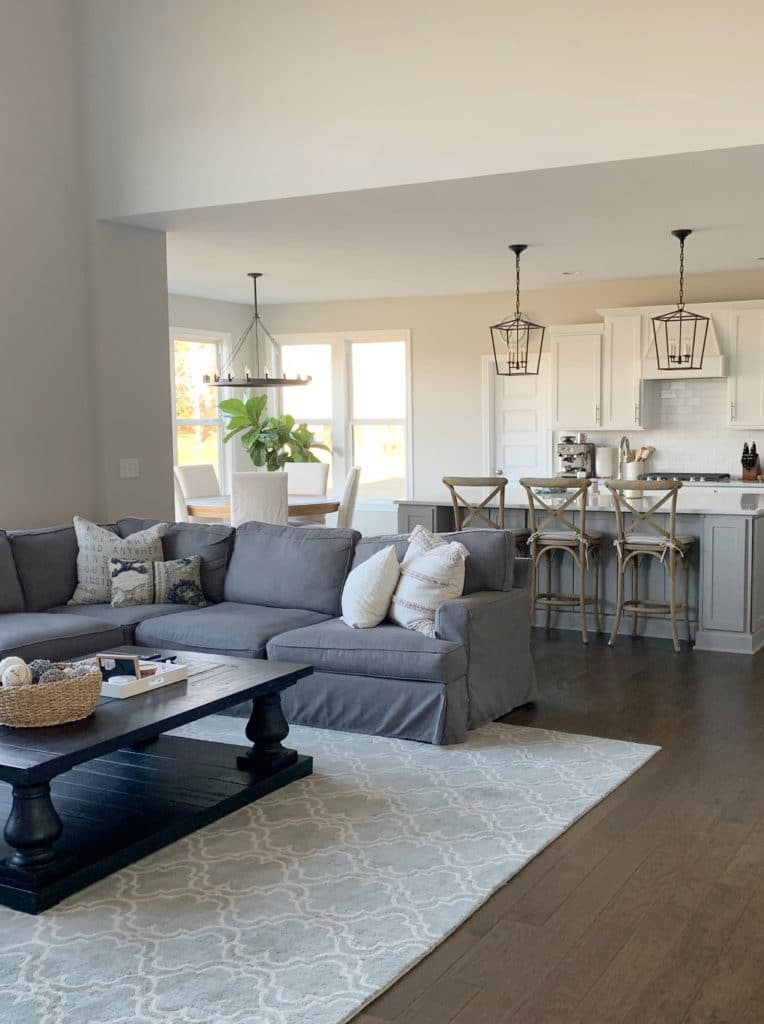 Open concept living room and kitchen, Sherwin Williams Agreeable Gray, grey sectional. White cabinets. Kylie M Interiors Edesign, client befor ephoto