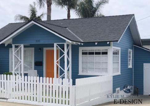 Exterior siding in blue paint colour, white trim, orange front door, dark gray black roof. Kylie M INteriors Edesign