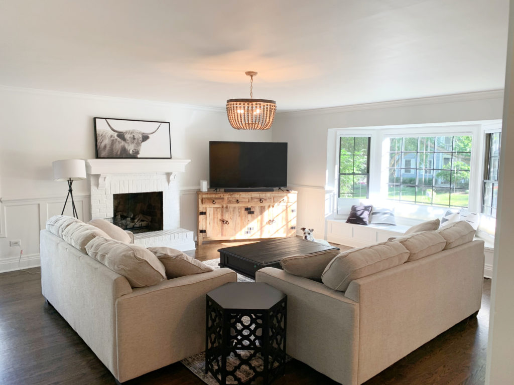 Living room beige sofa and loveseat, wood floor, Sherwin Williams Pure White, best soft white, north east exposure, brick fireplace. Kylie M Interiors client photo